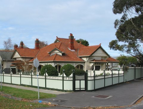 white and green fencing around house