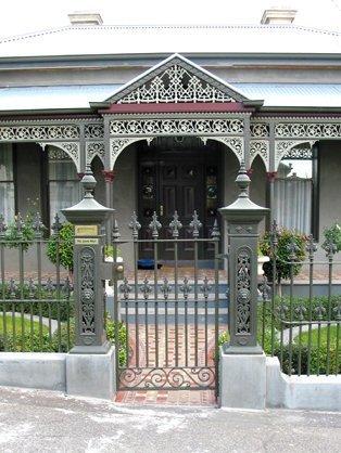 Cast iron pedestrian feature gate with cast iron verandah by Perry Bird Pickets