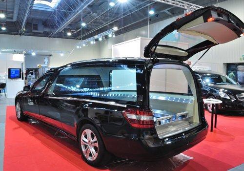 esposizione auto nera su un tappeto rosso con baule aperto