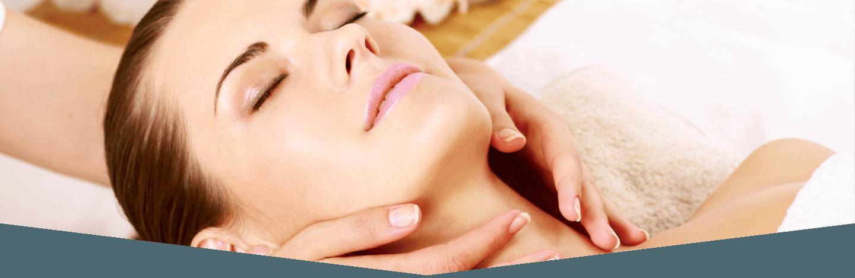 Viso di una donna mentre delle mani la massaggiano sul collo