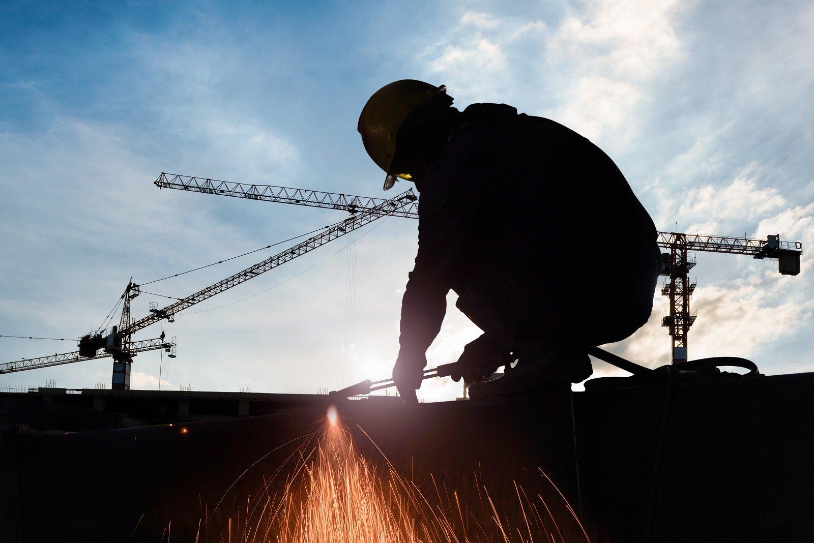 operaio lavora in cantiere, gru sullo sfondo