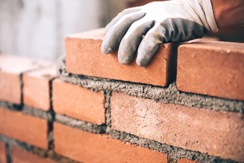 muratore costruisce un muro di mattoni