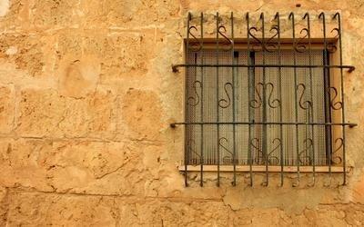 finestra con inferriate e muro ocra