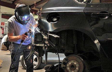Worker welding car body in Rochester