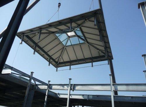 un tetto che sta per essere posizionato su dei pali strutturali in ferro