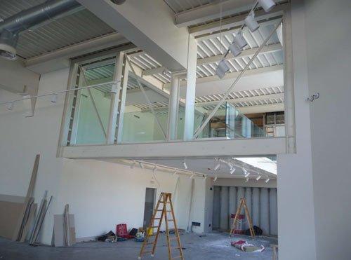 Delle scale da lavoro in legno e sopra delle finestre con delle vetrate