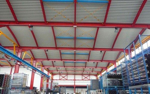 Delle strutture in ferro di color rosso reggono il tetto di magazzino