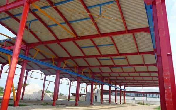 Delle strutture in ferro di colore rosso che reggono il tetto di un edificio in fase di costruzione