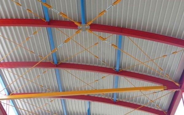Delle strutture in ferro rosse, arancioni e blu che reggono un tetto