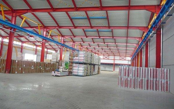 Delle strutture in ferro rosse azzurre che reggono il tetto di un magazzino