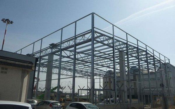 una  struttura in ferro di un edificio in fase di costruzione e delle macchine parcheggiate
