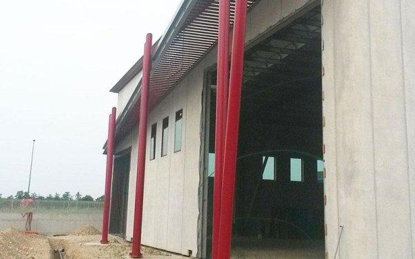 Dei pali rossi vicino all'entrata di uno stabile in costruzione
