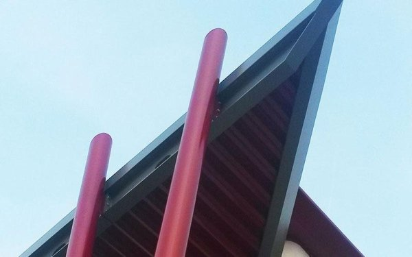 Due pali rossi vicino all' un angolo di un tetto