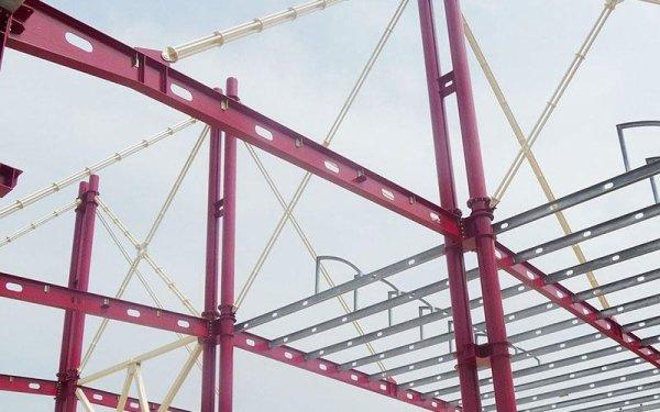 delle travi rosse in ferro e delle strutture di uno stabile in costruzione