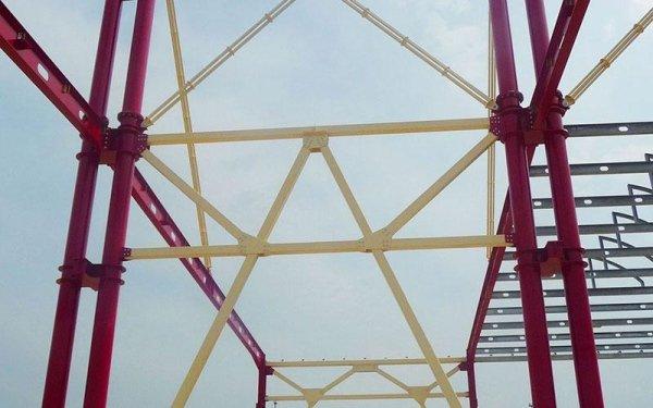 Delle strutture in ferro di color giallo che si congiungono a una struttura di color rosso