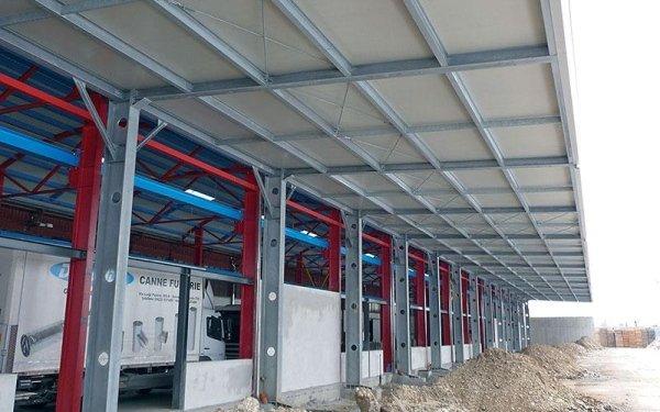 Una tettoia sorretta da delle strutture in ferro di un edificio che produce canne fumarie