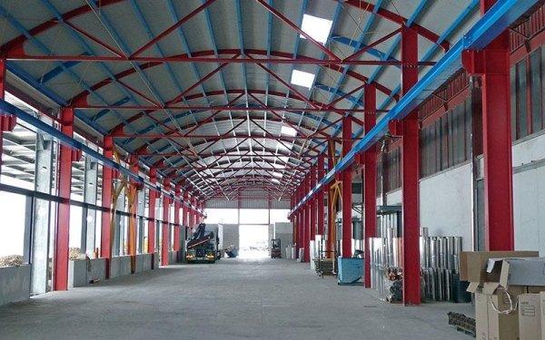 Delle travi rosse e blu in ferro che sorreggono il tetto di un magazzino
