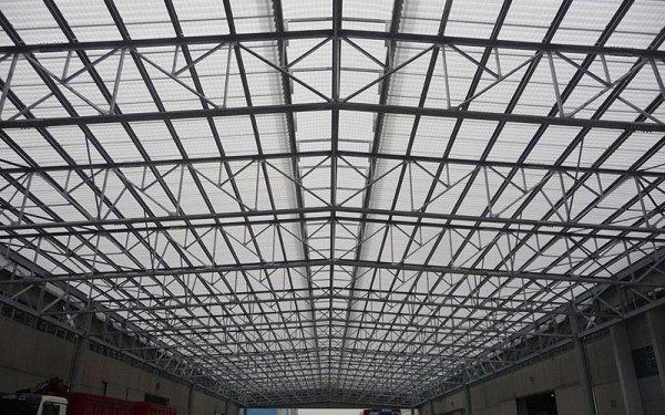 Una struttura in ferro a rete che sorregge il tetto di un edificio