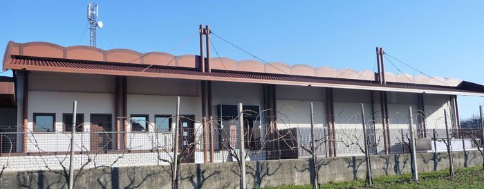 Dei pali in ferro con una recinzione e vista di un edificio