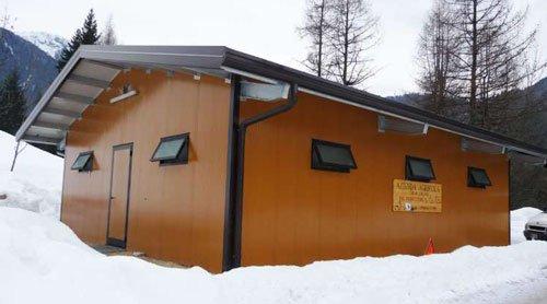 Un piccolo edificio di color marrone in una zona innevata con degli alberi