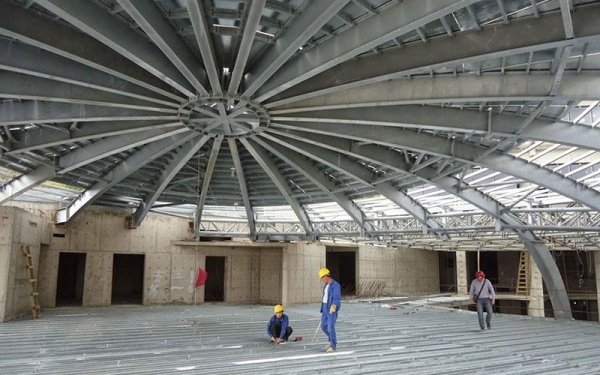 Delle strutture in ferro curve che fungono da tetto di un edificio in fase di costruzione e dei muratori al lavoro