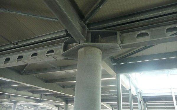 una grossa colonna in cemento con delle travi che regge il tetto di un edificio in fase di costruzione