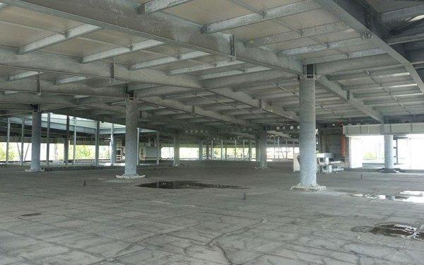 Delle colonne grosse  in cemento con delle travi che reggono il tetto di un edificio in fase di costruzione