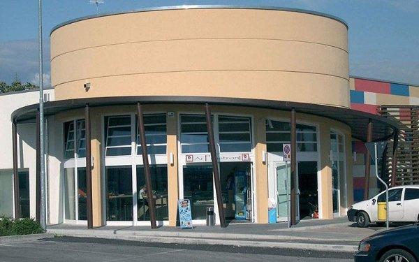 Un edificio color sabbia con una tettoia marrone e  delle vetrine sotto