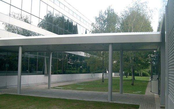 Una copertura sorretta da dei pali che congiunge due edifici e vista di due aree verdi con degli alberi