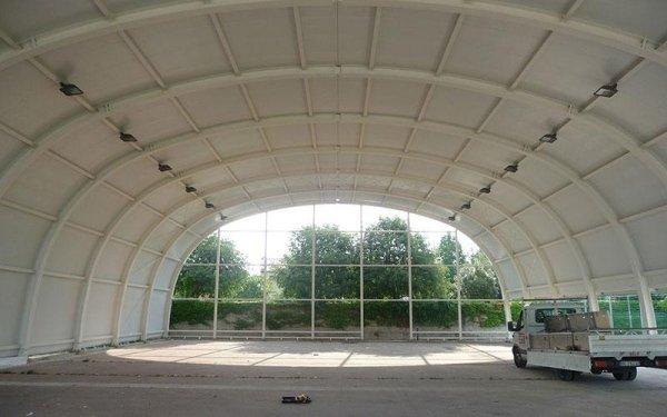 Delle strutture in ferro di color bianco curve che reggono il tetto di un edificio in fase di costruzione