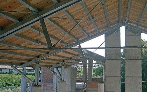 Delle travi e strutture in ferro che reggono un tetto in legno di un edificio in fase di costruzione