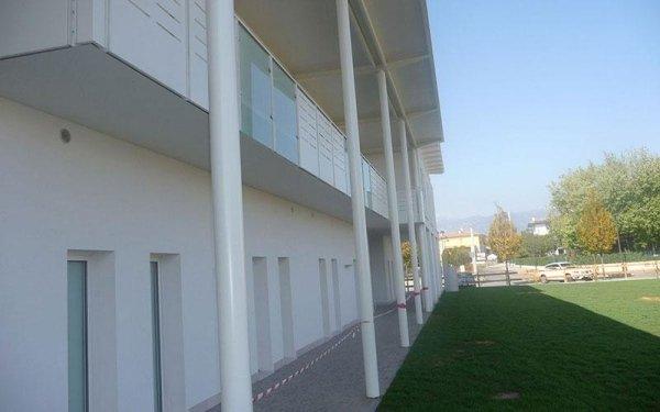 Esterno di un edificio bianco con dei pali che reggono il tetto e vista di un balcone