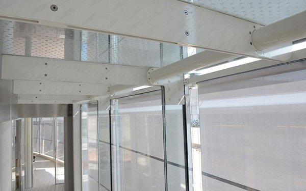 Delle vetrate e delle travi in ferro di colore bianco all'interno di un edificio