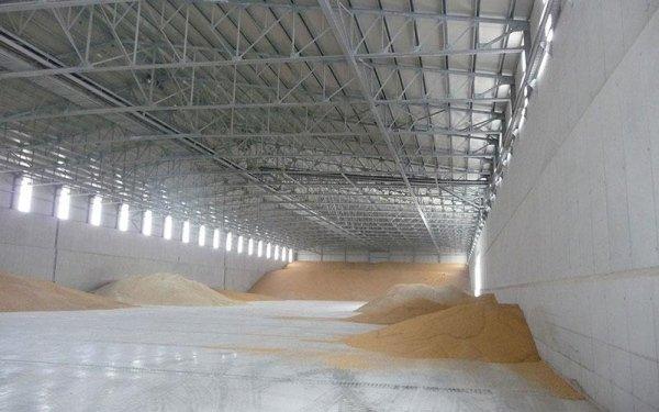 Interno di un edificio con dei cumuli di sabbia e una struttura in ferro che regge il tetto