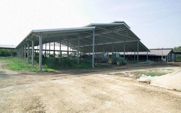 Delle travi in ferro che reggono il tetto di un edificio con sotto delle macchine agricole