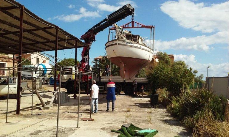 Barca retta da un braccio meccanico prima della riparazione