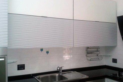 Cucina con cassoni in nobiliato bianco e ante in MDF effetto onda laccate lucide.
