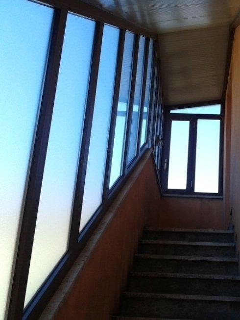 chiusura vano scale con finestre in alluminio effetto legno