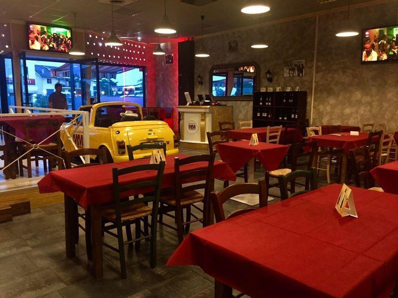 tavoli apparecchiati e auto gialla in vetrina