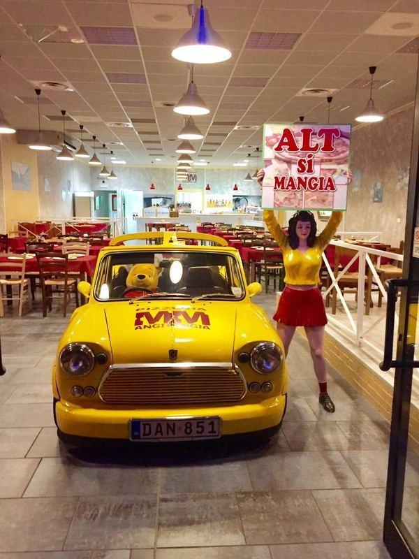 zona della pizzeria con una macchina gialla