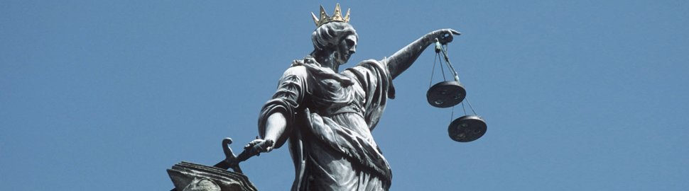 Conceptual image of justice - stature holding sword and scales