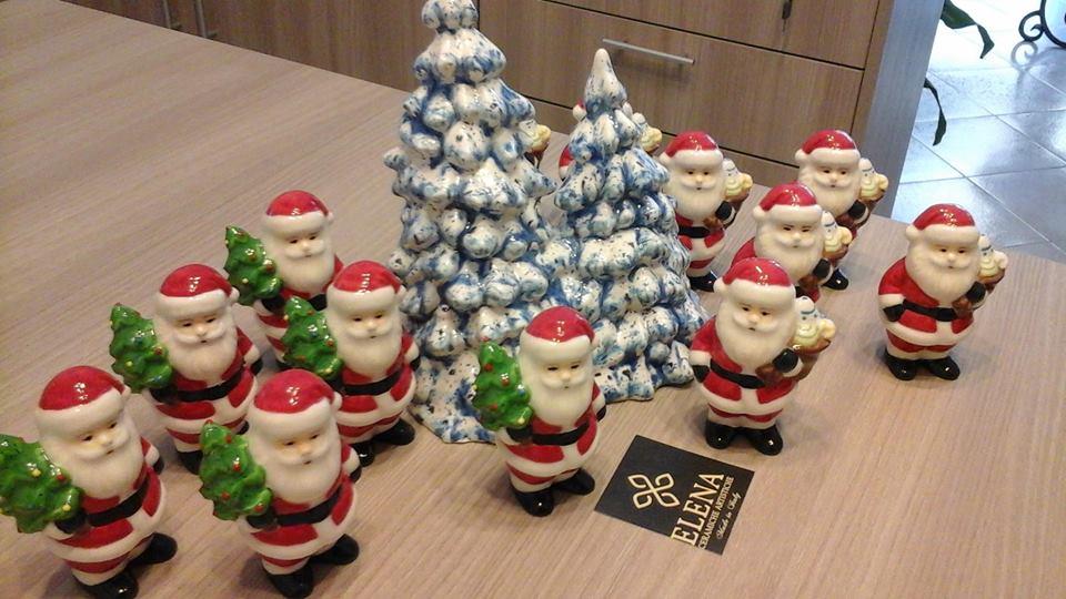 dei babbi Natale e un albero in ceramica colorati