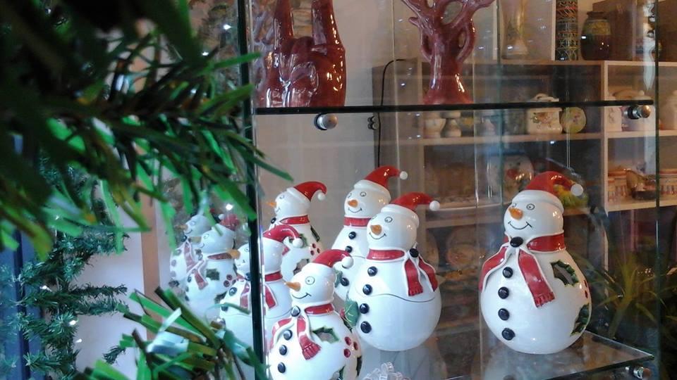dei pupazzi di neve colorati in ceramica in una vetrina