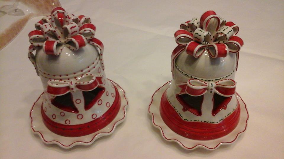 due campanelle rosse e bianche di ceramica con un fiocco