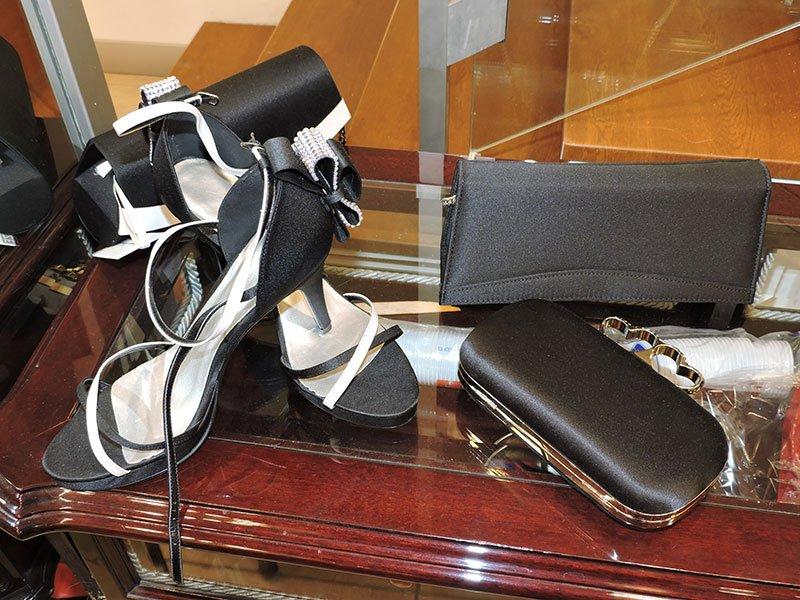 Scarpe di salon in raso nero con dettagli bianchi e tre borsette di festa di colore nero, piccoli e discreti