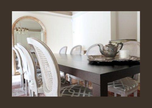 un tavolo in legno scuro e delle sedie di color bianco