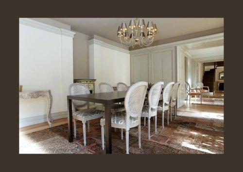 un tavolo lungo con delle sedie in legno di color bianco
