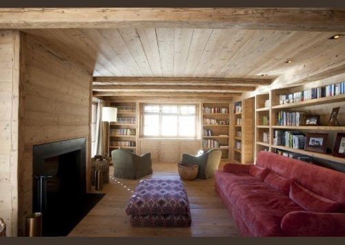 una sala con un divano di color rosso e pavimento in legno