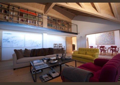 una sala con dei divani in vari colori, pavimento e il tetto in legno