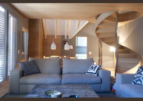 una sala con due divani e vista delle scale in legno